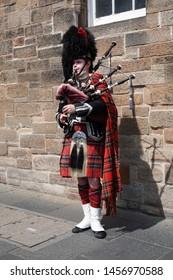 Edinburgh, Scotland, 18th July 2019. A traditionally dressed Scotsman playing the bagpipes on a street in Edinburgh Scotland.