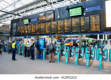 EDINBURGH, SCOTLAND - 20 APRIL 2016:  Edinburgh Waverley railway station.  People are moving through the turnstiles.  The time table is also in shot.