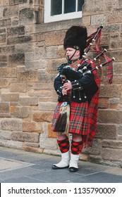 Edinburgh, Scotland - April 2018: A Scottish piper man dressing in Scottish traditional tartan kilt playing a bagpiper at Royal Mile, touristic street of Old Town Edinburgh City in Scotland, UK