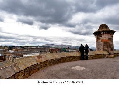 Edinburgh, Scotland - April 2018: Tourists overlooking scenic view of Edinburgh City from the Esplanade in front of Gatehouse, the main entrance to Edinburgh Castle, Scotland, UK