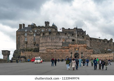 Edinburgh, Scotland - April 2018: Tourists walking at the Esplanade in front of Gatehouse, the main entrance to Edinburgh Castle, popular tourist attraction and landmark of Scotland in Edinburgh, UK