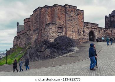 Edinburgh, Scotland - April 2018: Tourists at Foog's Gate, principle gate to the Upper Ward inside Edinburgh Castle, popular tourist attraction and landmark of Edinburgh, capital city of Scotland, UK