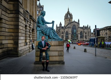 Edinburgh, Scotland - April 27, 2017: Bagpipe player with traditional scottish highlander robes playing on the Royal Mile, with St. Giles catherdral in the background