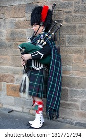 EDINBURGH, SCOTLAND - AUG 12, 2015: A Scotsman Bagpiper wearing traditional Scottish highlander's kilt outfit plays music on Royal Mile in Edinburgh.