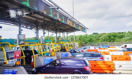 Edinburgh, Scotland - Aug 2014: View of many lanes of cars lining up to go through a highway toll booth during a summers day.