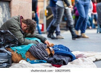 EDINBURGH, SCOTLAND - AUG 26, 2012: Unidentified local homeless white man sits on pavement in the city of Edinburgh on the Royal mile.