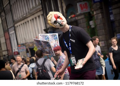 EDINBURGH, SCOTLAND - August 3, 2018: Man with a strange mask giving flyers for his show on Royal Mile during Fringe Festival.