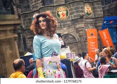 EDINBURGH, SCOTLAND - August 3, 2018: Drag queen giving flyers on Royal Mile during Fringe Festival.