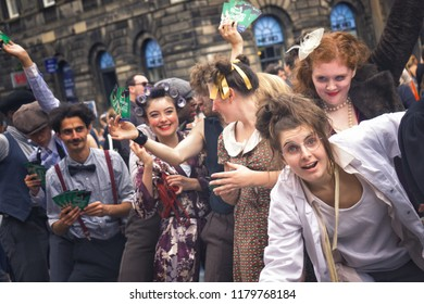 EDINBURGH, SCOTLAND - August 3, 2018: Troup of young people promoting their theatre play on Royal Mile during Fringe Festival.
