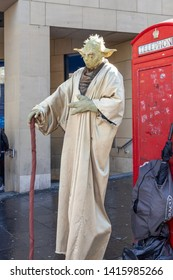 EDINBURGH, SCOTLAND – AUGUST 5, 2017: A 7 foot tall Yoda entertains passersby at the Edinburgh Festival Fringe.