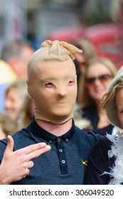 EDINBURGH, SCOTLAND - AUGUST 8, 2015: Man with stocking over head and hand formed like a gun on the Royal Mile during the Edinburgh International Fringe Festival