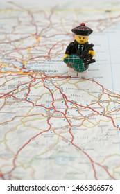 edinburgh, scotland - CIRCA Jul 2019: A lego bagpiper on a map of Scotland, placed next to Edinburgh