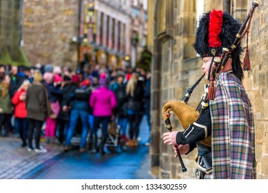 Edinburgh, Scotland - Dec 2018. Scottish bagpiper dressed in traditional red and black tartan dress playing bagpipe on the Royal Mile.