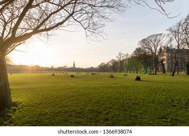 EDINBURGH / SCOTLAND,  February 20 2019, People watching sunset sitting on the green grass near university