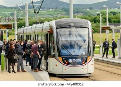 EDINBURGH, SCOTLAND -  JUNE 20, 2016: Commuters boarding a tramcar service  at Edinburgh Park to the west of the city.