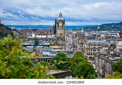 Edinburgh / Scotland — June 20, 2018: panoramic view of Edinburgh from Calton Hill with Princes street, the tower of Balmoral Hotel and Edinburgh Castle in the background on a cloudy morning