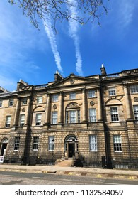 EDINBURGH, SCOTLAND - MAY 07 2018: Vapour trails in blue sky above elegant Georgian architecture of Bute House in Charlotte Square Edinburgh, official residence of the First Minister of Scotland