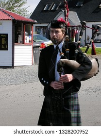Edinburgh / Scotland - May 12 2007: One Scottish male bagpiper walks alone in Edinburgh playing his bagpipes on sunny day.