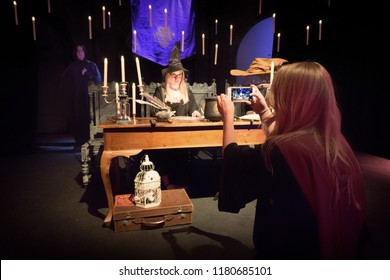 EDINBURGH, SCOTLAND - May 13, 2018: Two young women taking pictures dressing up as wizard in a Harry Potter display.
