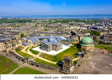 Edinburgh, Scotland - May 13, 2019:  View of Calton Hill and the city of Edinburgh below with the Firth of Forth waterway in the distance.