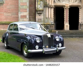 Edinburgh, Scotland - May 18, 2019;  An old vintage Rolls Royce automobile parked outside a church.