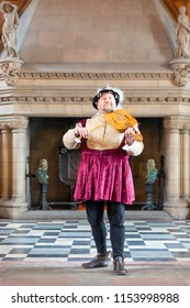 Edinburgh, Scotland - May 20, 2018: Minstrel in medieval costume playing a violin in historic room Edinburgh castle