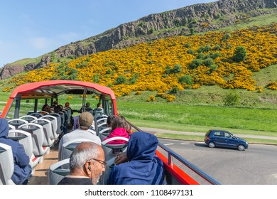 Edinburgh, Scotland - May 24, 2018: Sightseeing bus with tourists near science museum Dynamic Earth in front of mountain Arthurs Seat