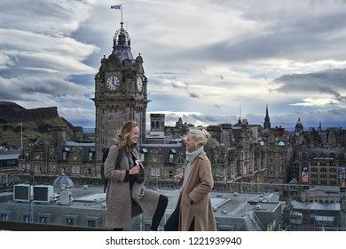 EDINBURGH, SCOTLAND - November 1, 2018: two young ladies drinking prosecco from rooftop of Edinburgh Grand Hotel. View of the Balmoral Hotel in the backgorund.