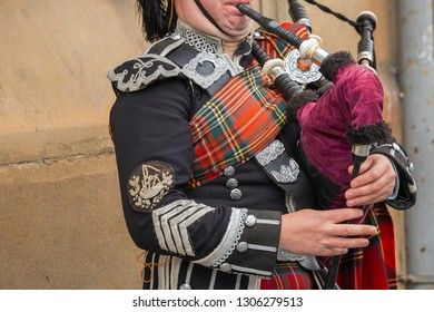 Edinburgh, Scotland - October 10 2017: Scottish bagpiper dressed in traditional red and black tartan dress stand. Edinburgh - Scotland