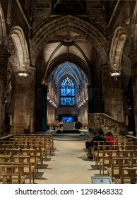 EDINBURGH, SCOTLAND - OCTOBER 15, 2018: Pews, stained glass windows, arches and amazing Gothic architecture in the beautifully lit  St Giles' Cathedral on the Royal Mile in Edinburgh, Scotland