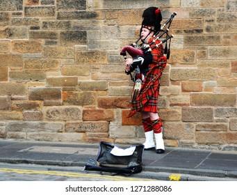 Edinburgh, Scotland - October, 2018: A street busker in Edinburgh plays the bag pipes in Scottish attire.