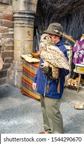 Edinburgh, Scotland - October 28, 2019: Man with his pet owl taking pictures with tourists in the city center of Edinburgh.