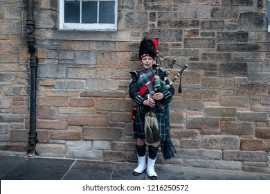 EDINBURGH, SCOTLAND, SEPT. 2018 , Scottish bagpiper dressed in traditional red and black tartan dress stand before stone wall. Edinburgh, the most popular tourist city destination in Scotland.