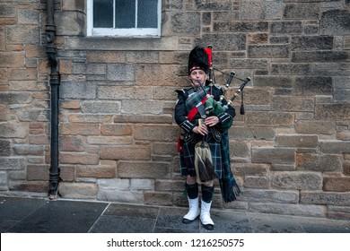 EDINBURGH, SCOTLAND, SEPT. 2018 , Scottish bagpiper dressed in traditional red and black tartan dress stand before stone wall. Edinburgh, the most popular tourist city destination in Scotland.