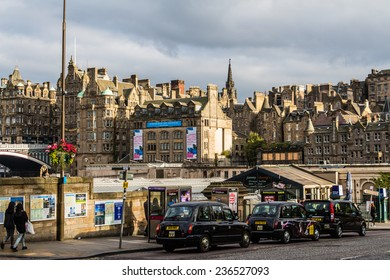 Edinburgh, Scotland - September 14, 2014: trio of black cab taxis waiting for pick up on Waverley Bridge on a sunny late summer afternoon.