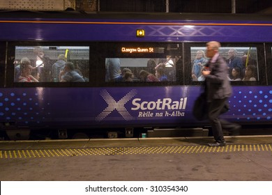 Edinburgh, Scotland, UK - 22 August 2015: man wearing suit running to catch crowded ScotRail Train during the busy Edinburgh Festival period