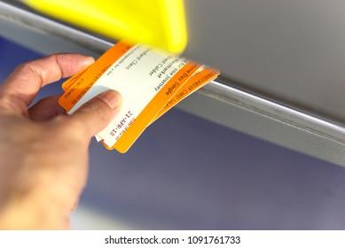 EDINBURGH, SCOTLAND, UK - APRIL 21, 2018. Close up of a hand retrieving travel tickets from a rail ticket dispensing machine