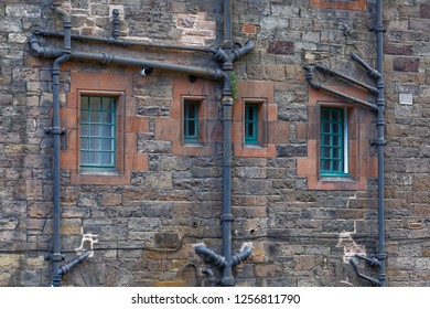Edinburgh, Scotland, UK - August 5: 2017: Plumbing pipe runs on the exterior of a building wall in Dean Village.