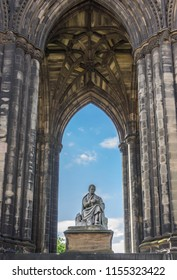 Edinburgh, Scotland, UK - June 13, 2012: Looking through Scott Monument with blue sky in back. Statue of Sir Walter Scott in center close up framed by dark stone pillars.