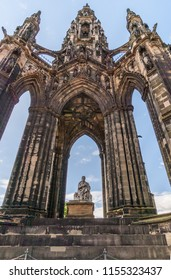 Edinburgh, Scotland, UK - June 13, 2012: Looking through Scott Monument with blue sky in back. Statue of Sir Walter Scott in center framed by dark stone pillars.