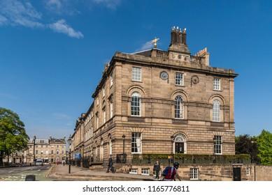 Edinburgh, Scotland, UK - June 14, 2012: Large brown upscale Georgian office building with chimneys on corner of Charlotte Square and N Charlotte Street under blue sky. Street scene with people.