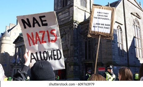 EDINBURGH, SCOTLAND, UK - MARCH 25, 2017. A crowd of protesters wave flags and signs at an antifascist demonstration on the Royal Mile.