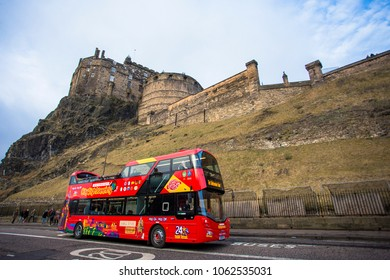 Edinburgh, Scotland United Kingdom - December 19 2016: Open top travel bus passing thru beneth Edinburgh Castle Scotland.