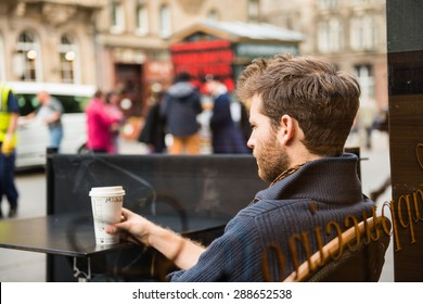 EDINBURGH, SCOTLAND / UNITED KINGDOM - MAY 24 2015 - Unidentified man sitting outside a cafe, watching the people of Edinburgh pass through.