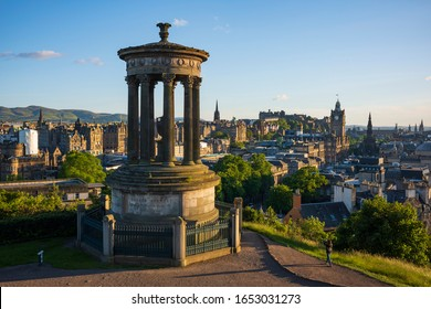 Edinburgh, Scotland/UK, June 21, 2019: The Edinburgh, Scotland skyline photographed from Calton Hill, a popular location for tourists, with the Dugald Stewart Monument in the foreground.