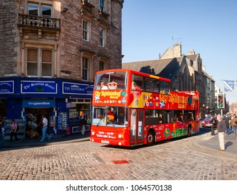 EDINBURGH, UK - AUG 8, 2012: Touristic red double-decker hop-on hop-off City Sightseeing tour bus at Royal Mile, a popular tourist attraction and the busiest tourist street in the Old Town