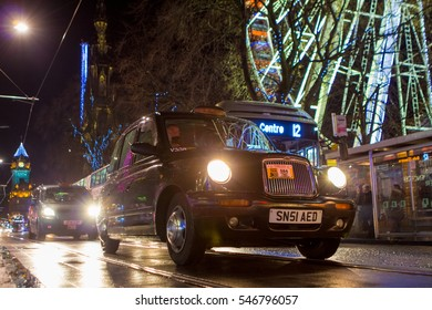 EDINBURGH, UK - DEC 22, 2016: Taxis and buses on Princess Street with Christmas lights reflecting in rainy road surface