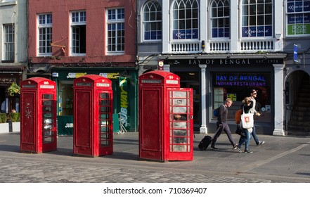 Edinburgh, UK - May 06, 2016: Iconic red phone boxes and tourists with bags in the center of the city