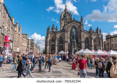 EDINBURGH, UNITED KINGDOM - AUGUST 15, 2017 - A boy advertises a theatrical performance along the Royal Mile of Edinburgh during the 70th anniversary of the Fringe Festival.