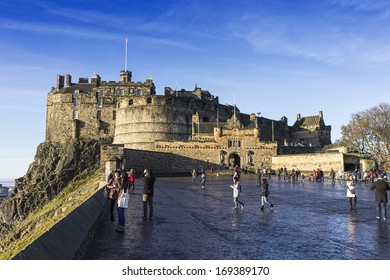 Edinburgh, United Kingdom - December 1, 2013: Several tourists in front of the main entrance of the castle of Edinburgh admiring the view of the city.